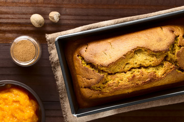 Fresh homemade pumpkin bread in pan, ingredients (pumpkin puree, cinnamon, nutmeg) on the side, photographed overhead (Selective Focus, Focus on the top of the bread)