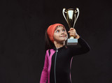 Happy little skater girl champion holds a winner's cup. Isolated on dark textured background. - 218665956