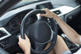 closeup of driver's hands on car steering wheel