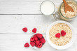 Oat flakes with fresh raspberries and milk on a white wooden table. healthy breakfast. top view