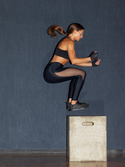 athletic fit woman jumping on crossfit box in gym © Schum
