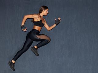 muscular woman in black sportswear running on dark background © Schum