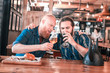 Football lovers. Two football lovers drinking craft dark beer and eating burgers while celebrating victory of their team