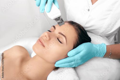 Fototapeta samoprzylepna Beautiful woman receiving ultrasound cavitation facial peeling. Cosmetology and facial skin care. facial treatment, face cleansing