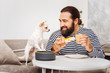 Cheesecake and latte. Bearded man eating cheesecake and drinking latte while looking at his little cute dog