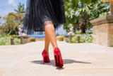Woman walking in red high heels - 218758191