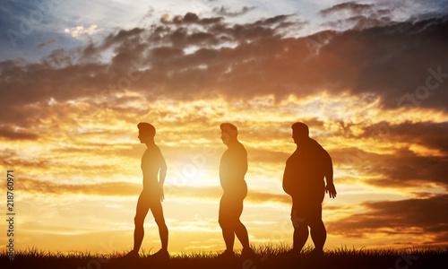Trzy sylwetki mężczyzn z różnych typów ciała na niebie słońca