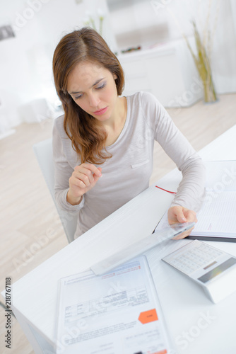 woman calculating bills on floor of living room - 218767118