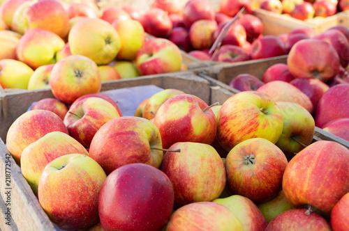 czerwone dojrzałe jabłka w drewnianych skrzyniach na sprzedaż na targu ulicznym