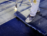 Worker preparing part of bitumen roofing felt roll for melting by gas heater torch flame - 218786319