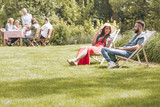 Summer vacation in green surroundings. People sitting on deck chairs and by the table in the garden. Copy space on green grass. - 218786932