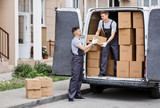 Two young handsome movers wearing uniforms are unloading the van - 218788300