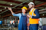 Low angle portrait of female factory worker giving tour of production workshop to businessman wearing hardhat and pointing away, copy space - 218793765