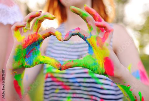 dziewczyna z rękami umazanymi kolorowymi palcami pokazuje serce na tle natury i słońca