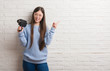 Young Chinese woman filming holding video camera very happy pointing with hand and finger to the side
