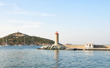 Macinaggio harbour with red lighthouse at sunset - 218814380