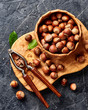 Hazelnut with nutcracker on olive wooden board. Nuts with green leaves. Top view.