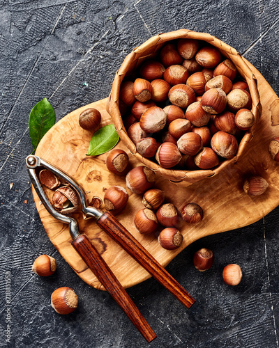 Hazelnut with nutcracker on olive wooden board. Nuts with green leaves. Top view. - 218831558