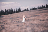Blonde woman in white dress on countryside meadow. Color tone filter effect used. - 218859590
