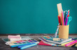 school supplies on wooden table on green background - 218904977
