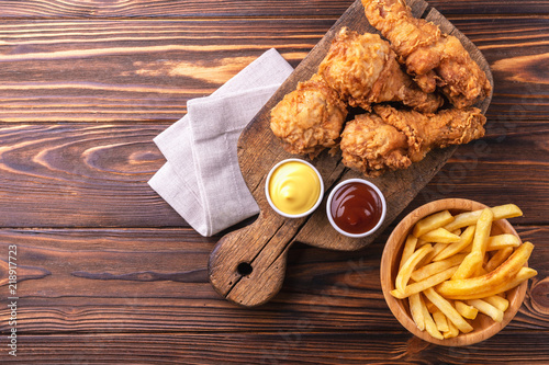 Crispy chicken legs and french fries potatoes. Fast junk food