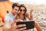 Cute loving couple make selfie by mobile phone on the beach outdoors.