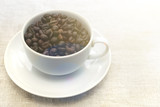 Good morning! Coffee beans in a white cup. Light textured background, toned photo. View from above. Copy space
