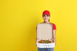 Delivery woman with pizza in cardboard box on yellow background