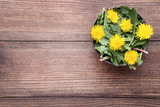 Yellow dandelions in bowl on brown wooden table - 218934993