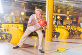 Bowling game. Nice aged man preparing to throw the ball while playing bowling - 218947100