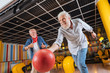 Great throw. Cheerful positive man smiling while throwing the bowling ball