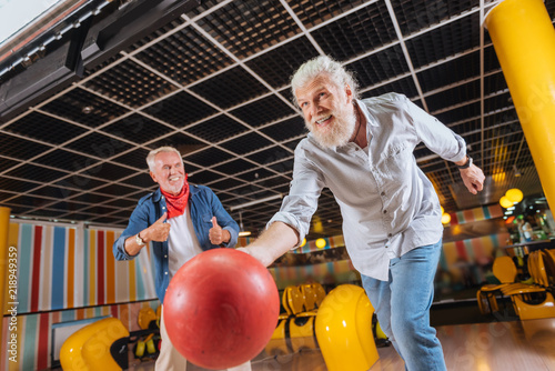 Great throw. Cheerful positive man smiling while throwing the bowling ball - 218949359