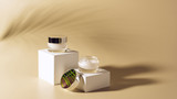 close up view of palm leaf shade, facial and body creams in glass jars on white cubes on beige background - 218950991