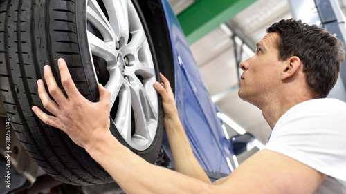 Reifenwechsel in einer autowerkstatt // tyre change in a car repair shop - worker assembles rims on the vehicle
