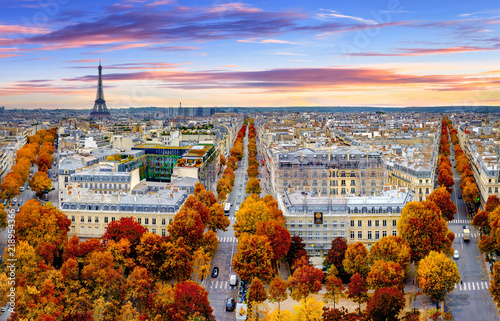 Zdjęcia na płótnie, fototapety na wymiar, obrazy na ścianę : Aerial view of Paris in late autumn at sunset.Red and orange colored street trees. Eiffel Tower in the background. Paris, France