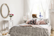 Mirror above white cabinet with roses in bedroom interior with patterned pink pillows on bed. Real photo