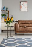 Sunflowers on table next to leather settee in apartment interior with poster and carpet. Real photo - 218957398