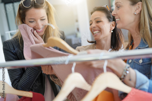 Girlfriends having fun shopping at clothing store