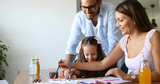 Mom and dad drawing with their daughter - 218994178