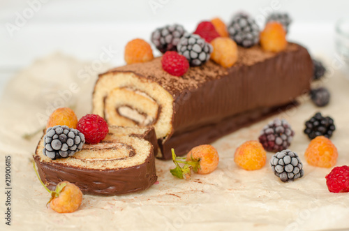 Wall mural Biscuit roll with raspberries and frozen blackberries on the table