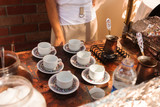 A waiter woman cooks Turkish coffee on the street in a mobile trolley and pours it over the cups.