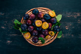 Fresh plums with leaves. Fruits. On a black wooden background. Top view. Free space for your text. - 219015591