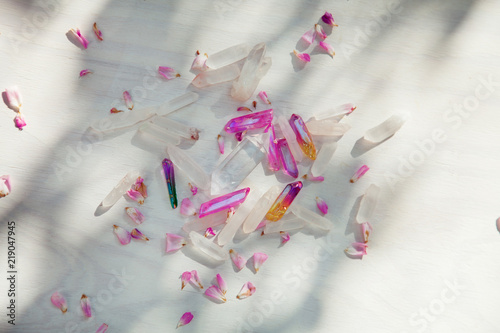 Foto Murales Colorful quartz crystals with pink rose leaves on wooden structure, flat lay background