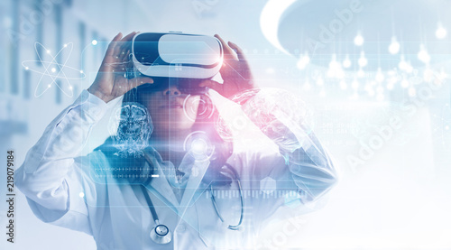 Medical technology concept. Mixed media. Female doctor wearing virtual reality glasses. Checking brain testing result with simulator interface. © ipopba