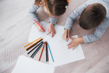 Children lie on the floor in pajamas and draw with pencils. Cute child painting by pencils - 219079753