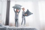 Children in soft warm pajamas playing in bed - 219079993