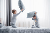 Little boy and girl staged a pillow fight on the bed in the bedroom. Naughty children beat each other pillows. They like that kind of game - 219080117