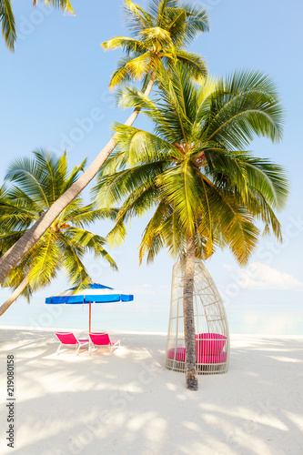 Leinwanddruck Bild Chairs And Umbrella In Palm Beach - Tropical Holiday concept, vertical composition