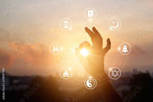 Woman hands praying for blessing from god and religions icon on sunset background