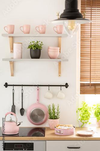 Prawdziwe zdjęcie wnętrza kuchni z pastelowymi różowymi kubkami i miskami na półkach, świeżymi roślinami i domowym biszkoptem na kontuarze
